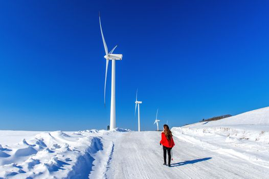 Beautiful girl walking in winter landscape of sky and winter road with snow and red dress and wind turbine.