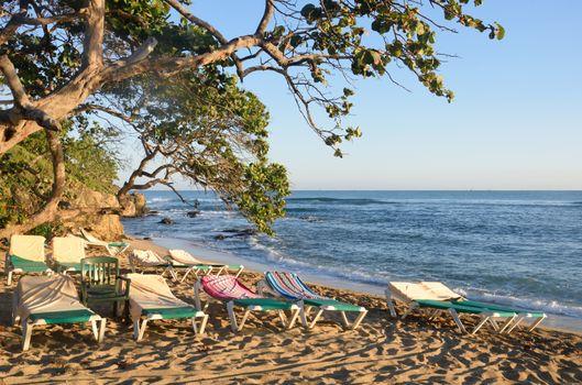 Empty sunbeds by caribbean beach