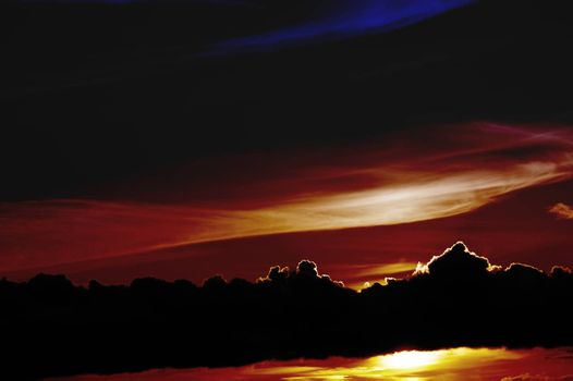 The abstract toning of a bright colorful sunset behind a distinctive cloud band.