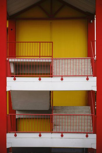 A colorful and striking sidewall of a shopping center with an external staircase to the first floor.