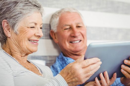 Senior couple smiling while using digital tablet in bedroom