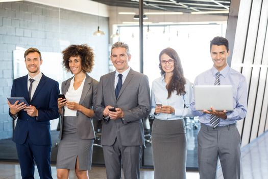 Businesspeople standing in a row and using mobile phone, lap top and digital tablet in offic