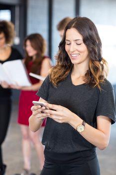Businesswoman text messaging on smartphone