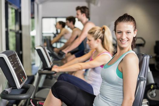 Fit people doing exercise bike at gym