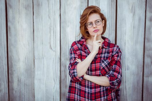 beautiful hipster woman thinking, with her finger to her face, against a wooden background