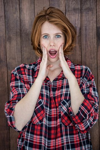 shocked hipster woman looking into the camera on a wooden background