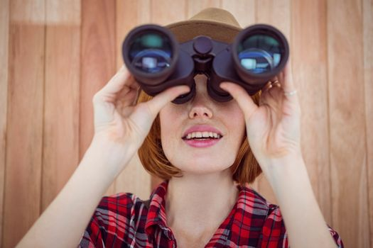smiling hipster woman looking through binoculars against a wooden background