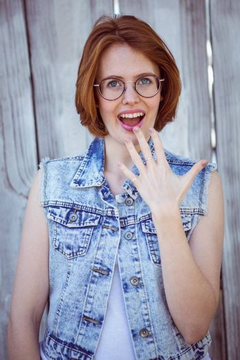 shocked hipster woman smiling at the camera, against a wooden background