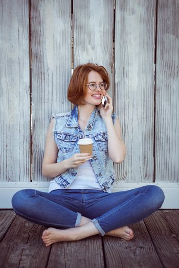 smiling hipster woman sitting on the phone and holding a coffee