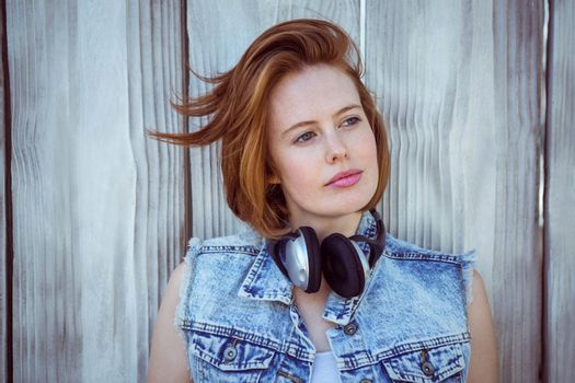 beautiful hipster woman looking into the distance against a wooden background