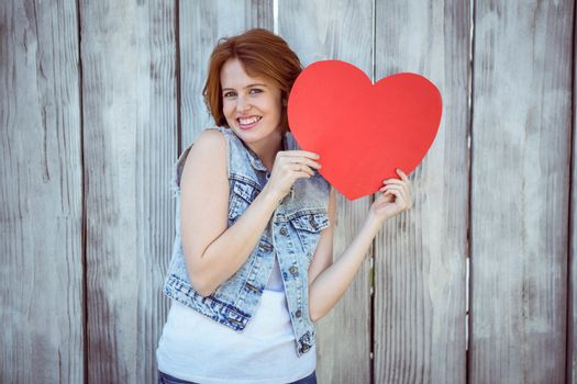 smiling hipster woman holding a heart against a wooden baackground