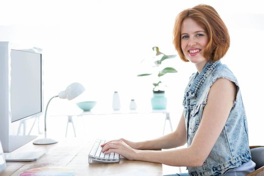 smiling hipster woman sitting at her desk , on the computer