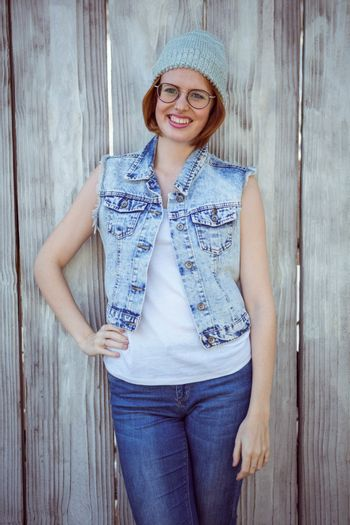 smiling hipster woman wearing a beanie hat with her hand on her hip