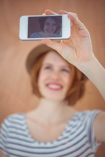 smiling hipster woman taking a selfie against a wooden background