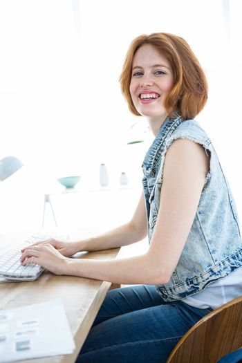 smiling hipster woman sitting at a desk with a computer