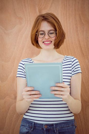 smiling hipster business woman on a tablet computer, against a wooden background