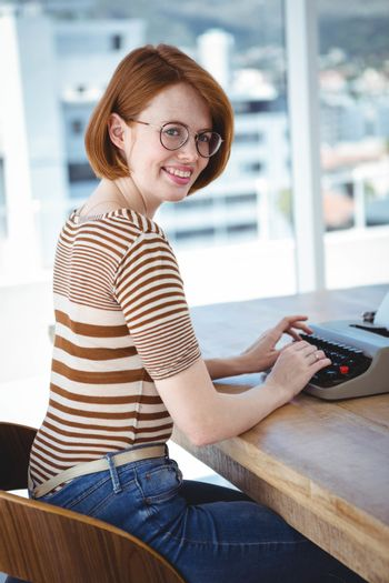 hipster typing on a typewrite that is on a wooden desk