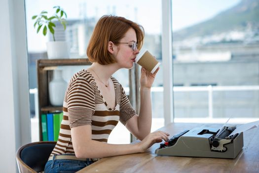 hipster business womn sitting on her typewriter and drinking cofee