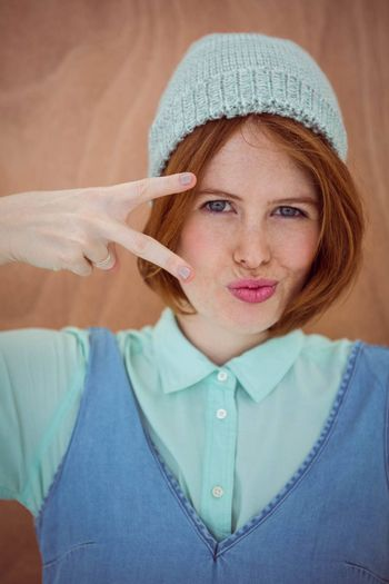 smiling hipster woman wearing a beanie hat with her hand to her face