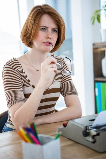 thoughtful hipster woman, sitting at her desk with a typewriter