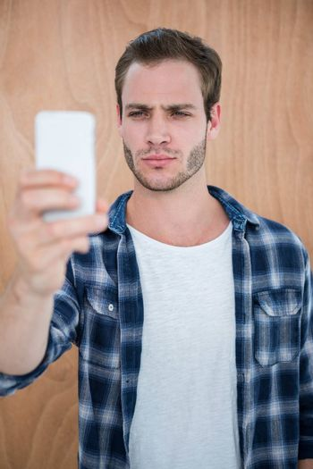 Handsome hipster taking a selfie on a wooden background