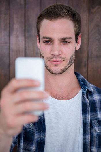 Handsome hipster looking at smartphone on wooden background