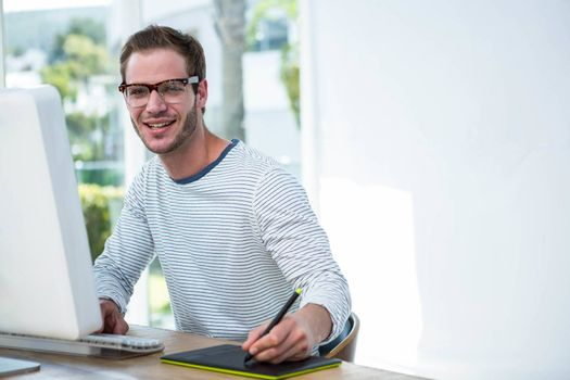 Handsome man working on computer in a bright office