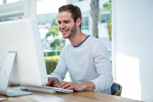 Handsome hipster working on computer in a bright office
