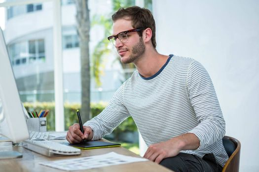 Handsome man working on computer and taking notes in a bright office
