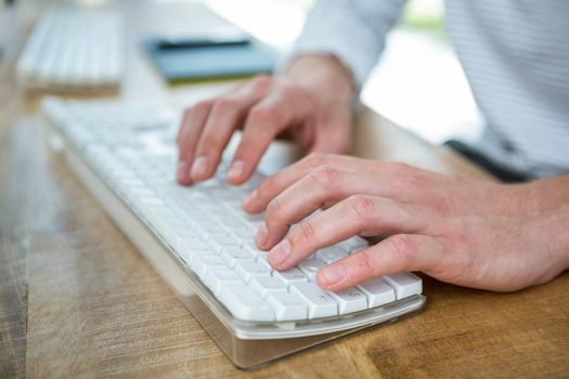 Masculine hands typing on keyboard in a bright office