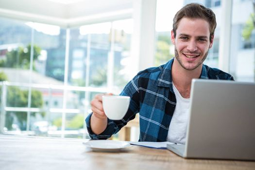 Handsome man working on laptop with cup of coffee in a bright office