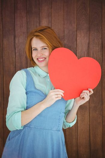 Pretty hipster holding heart on wooden background