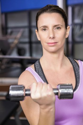 Determined woman lifting dumbbell