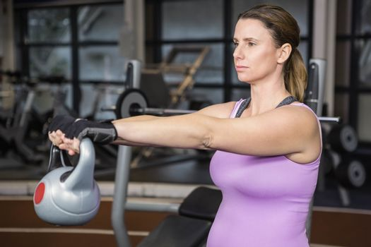 Determined woman lifting kettlebell