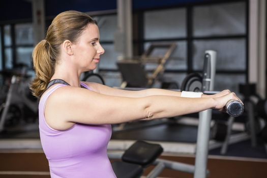 Determined woman lifting dumbbells