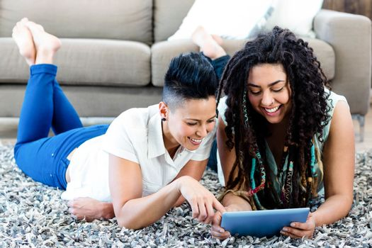 Smiling lesbian couple lying on rug and using digital tablet in living room