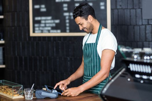 Handsome barista using cash register