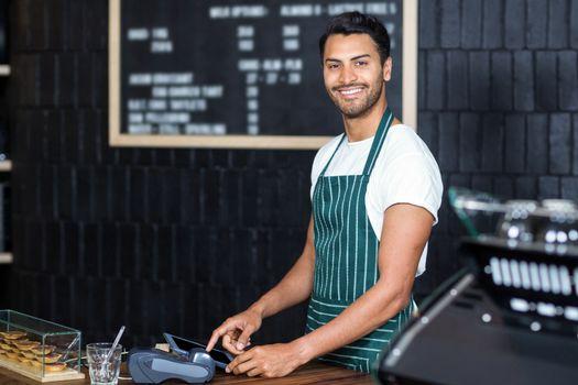 Pretty barista using cash register