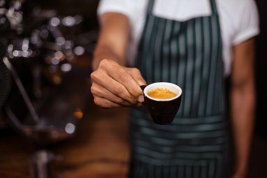 Barista offering an espresso