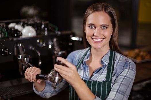 Pretty barista pressing coffee for coffee machine