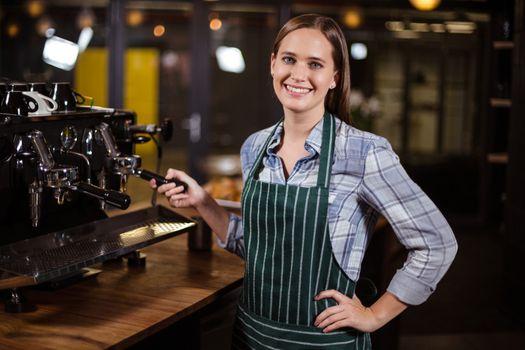 Pretty barista making coffee with coffee machine