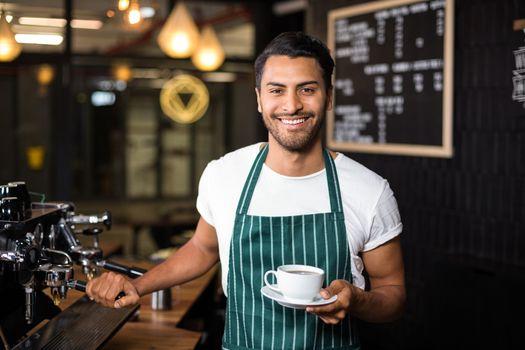 Smiling barista making coffee with coffee machine