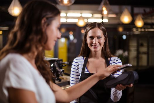 Smiling woman paying with smartphone