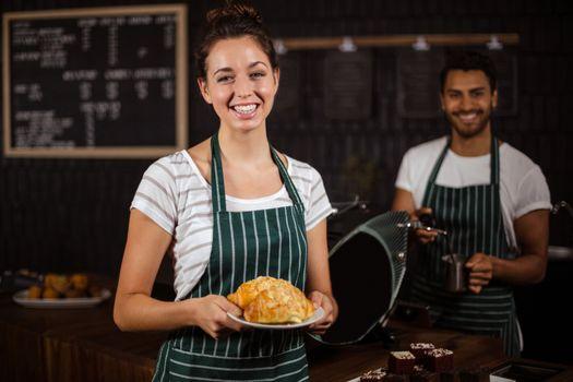 Smiling barista holding croissants