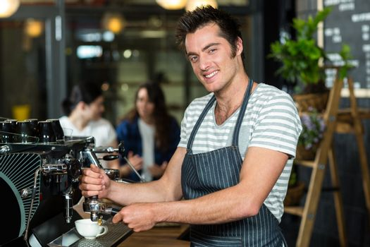 Smiling barista making coffee