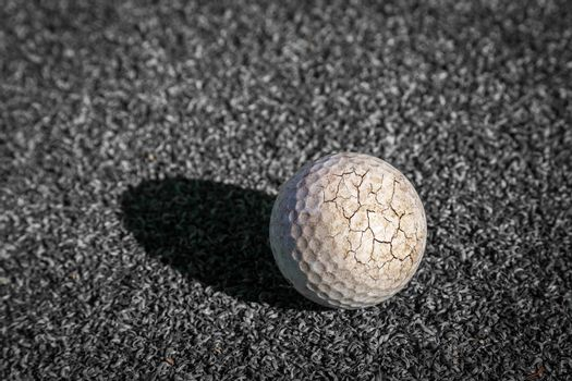 Crack golf ball with sunlight and shadow put on putting green in no color.
