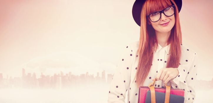 Smiling hipster woman holding book belt  against large city on the horizon