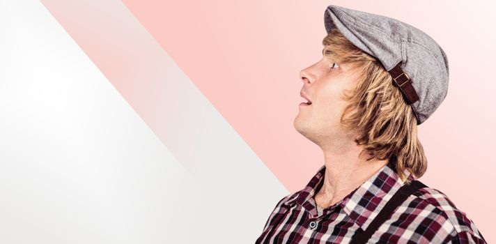 Side view of surprised blond hipster smiling  against grey background