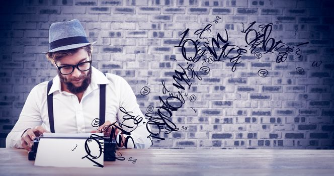 Hipster wearing eye glasses and hat working on typewriter against grey brick wall