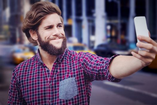 Hipster taking selfie against wooden wall against blurry new york street